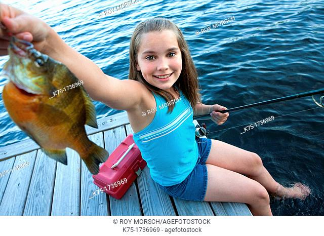 Young girl proudly shows off fish she caught