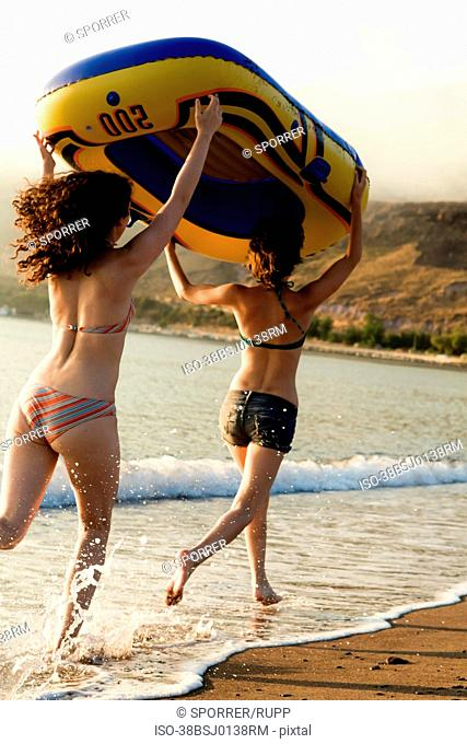 Women carrying inflatable boat on beach