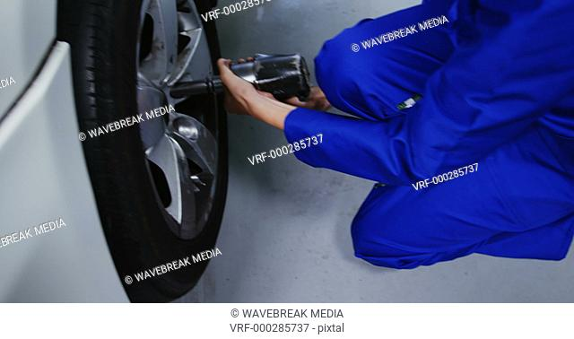 Female mechanic fixing a car wheel