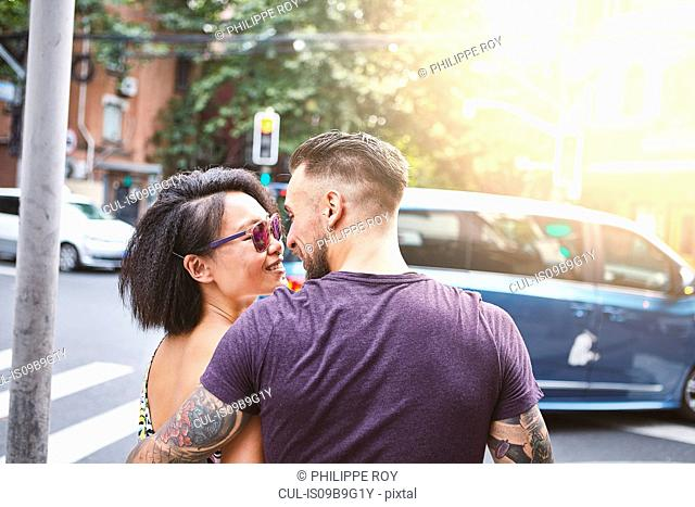 Multi ethnic hipster couple strolling along street, Shanghai French Concession, Shanghai, China