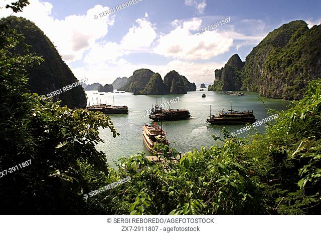 Ships sailing in the Halong Bay near Hang Sung Sot cave. A climber points to limestone cliffs in Halong Bay, Vietnam. Junks at Halong Bay in Viet Nam seen from...