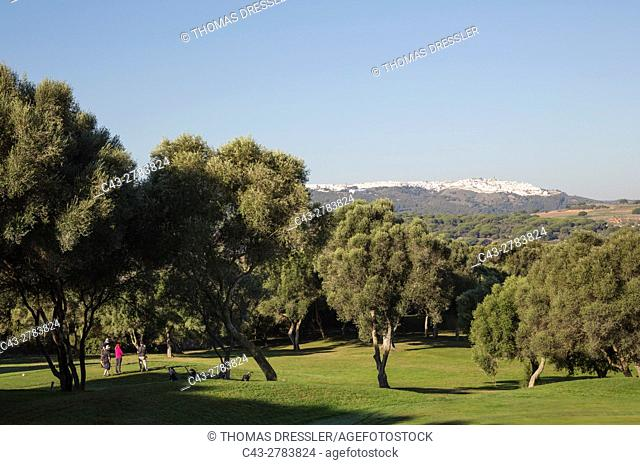 Golfers at the golf course of Montenmedio Golf & Country Club with the brilliant white hilltop town of Vejer de la Frontera in the background