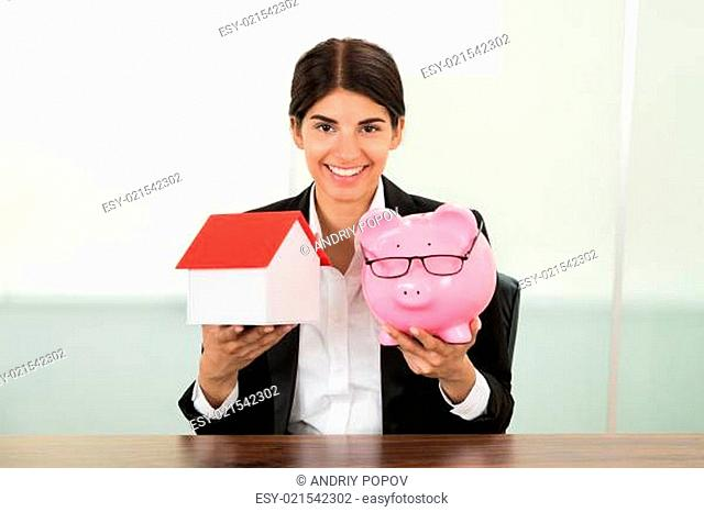 Young Happy Businesswoman Holding House Model And Piggybank In Hands