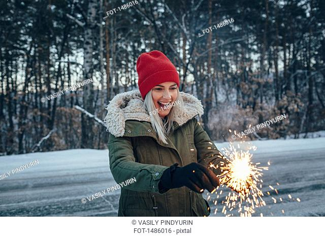 Happy woman holding sparklers while standing on field during winter