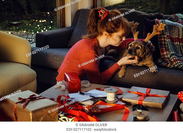 Young woman taking a break from wrapping presents to show her pet dog some affection. The dog is wearing antlers
