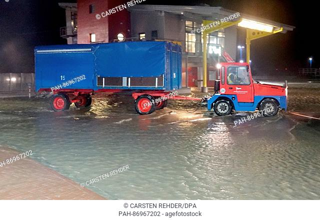 """A tractor drives through water at the ferry port in Dagebuell, Germany, 4 January 2017. Storm """"""""Axel"""""""" is causing storm tides on the coasts of the North and..."""