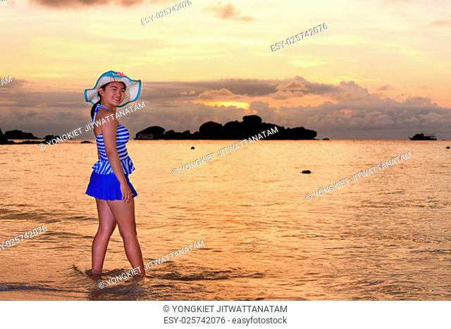 Visitors woman in a blue swimwear and hat standing looking the beautiful landscape of sky over the sea happily on the beach during sunrise at Koh Miang Islands