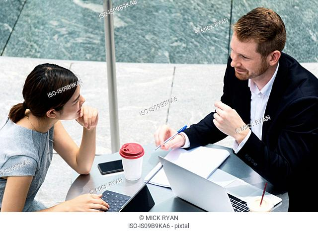 Young businessman and woman with laptops meeting at sidewalk cafe