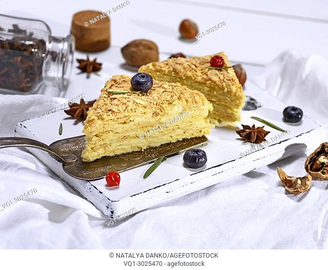 two baked cakes Napoleon with cream on a white wooden board, close up