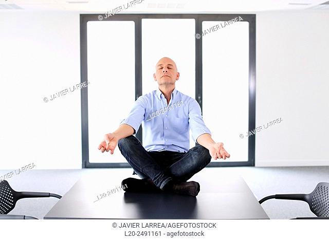 Executive doing Yoga. Empty office. Meeting room