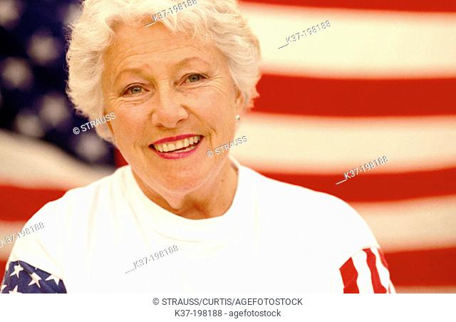 Patriotic mature American woman in front of U.S. flag
