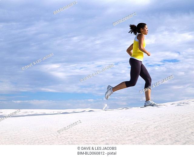 Mixed Race woman running on sand dune