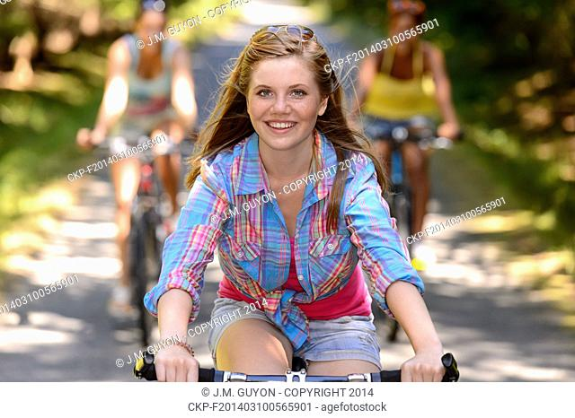 Teenage girl riding bike with friends on countryside road