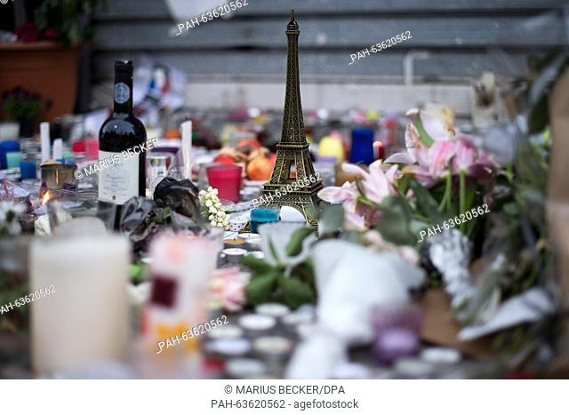 A small Eiffel Tower stands among flowers and candles in front of the restaurant 'Le Petit Cambodge' in Paris, France, 16 November 2015