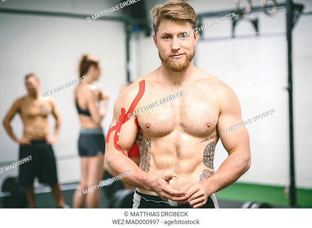 Young muscular man in gym with taped shoulder