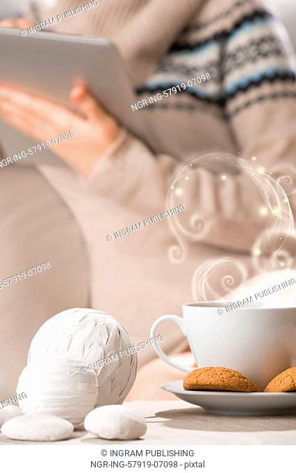 Cup of hot beverage tea or coffee with oat cookies and a lot of vapor standing on table at cafe or home. Female sitting on background