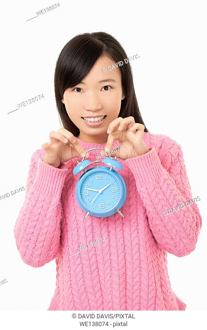 Beautiful Chinese woman holding a blue alarm clock isolated on a white background
