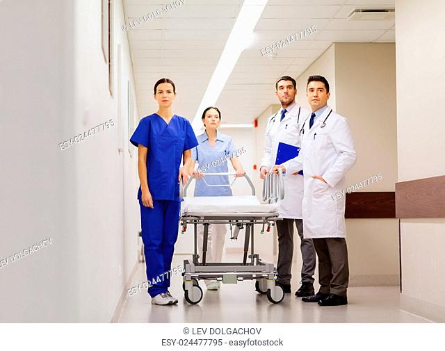 clinic, profession, people, health care and medicine concept - group of medics or doctors with gurney at hospital corridor