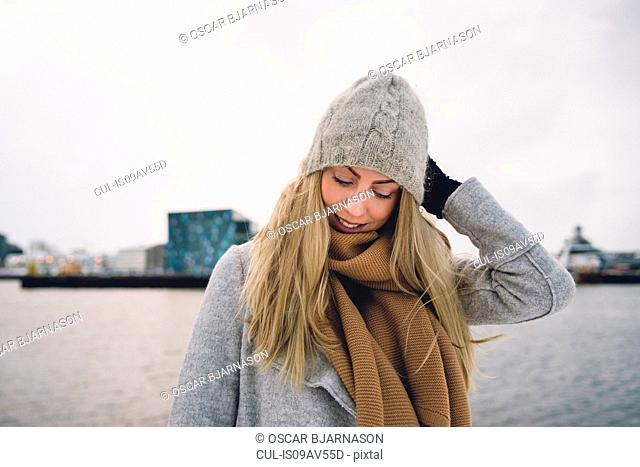 Young woman wearing woollen hat and scarf by water looking down smiling