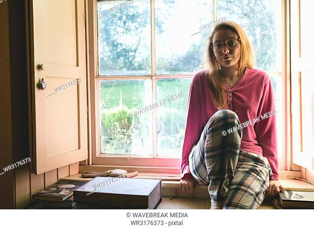 Woman relaxing near window at home