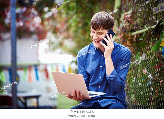 A young man sitting outdoors holding an open laptop in his hand and a cellphone to his ear