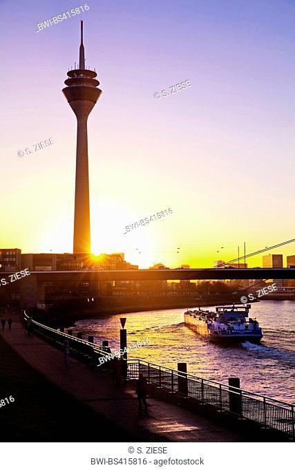 Rheinturm and transport ship on Rhine river at sunset, Germany, North Rhine-Westphalia, Duesseldorf