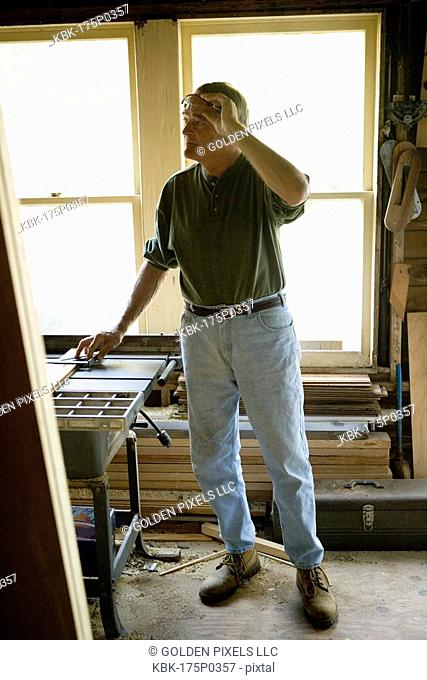 Mature man in tool shed surrounded by lumber and carpentry tools