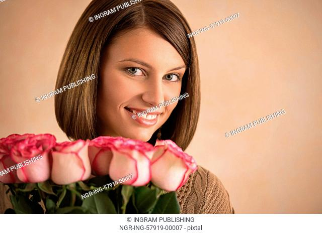 Pretty brunette woman holding bunch of roses