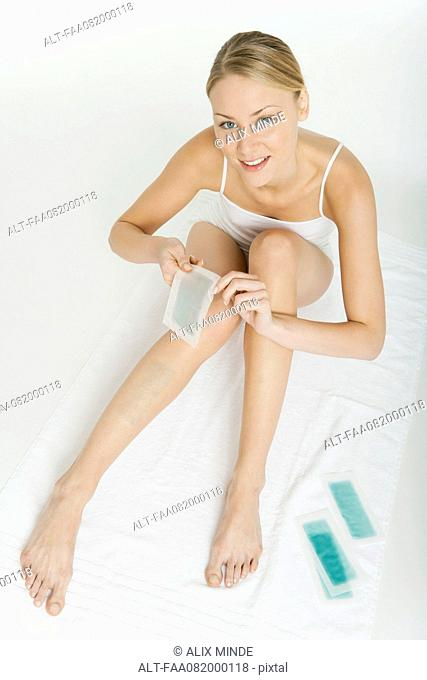 Young woman waxing her legs with cold wax strips