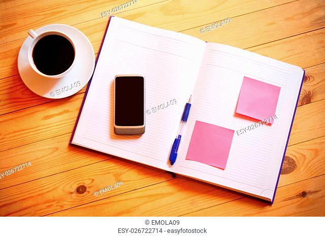 Cup of coffee, pen, opened organizer and smartphone on wooden background