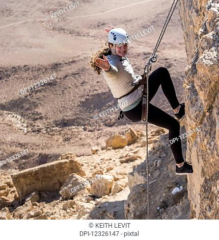 A young woman rappelling into Ramon Crater, Ramon Nature Reserve; Mitzpe Ramon, South District, Israel