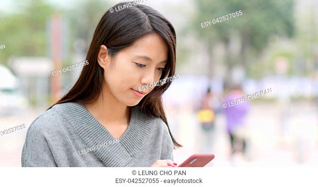 Young woman sending audio message on cellphone