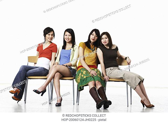 Portrait of four young women sitting on chairs