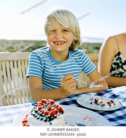 Portrait of a smiling boy eating a cake, Sweden
