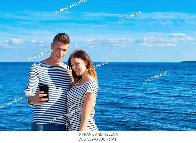 Young couple standing by sea, taking self portrait using smartphone