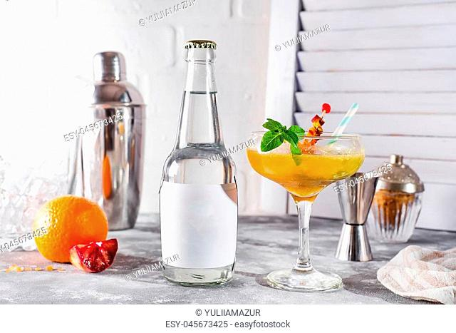 Cocktail with orange juice, Bar accessories with a bottle of tonic and a place under the text on the bottle on wooden background