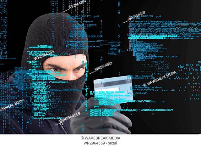 Cyber criminal wearing a hood is holding a credit card against matrix digital rain background
