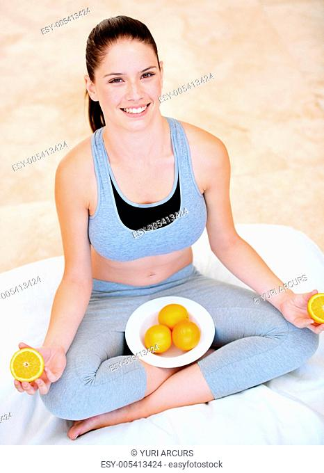 Playful young woman holding orange halves and sitting with a bowl of oranges