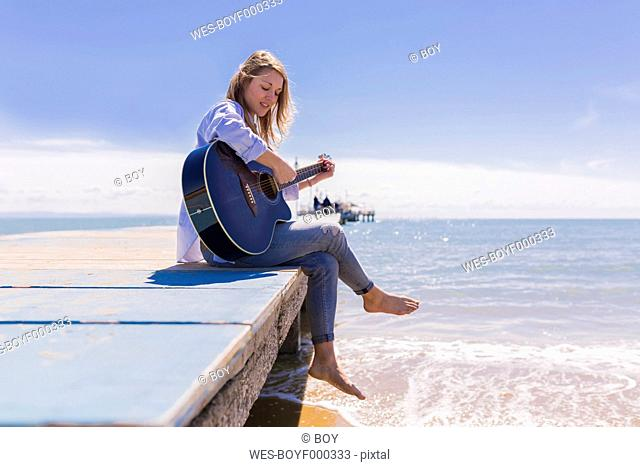 Young woman with guitar sitting on jetty