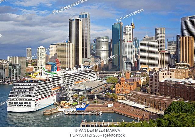 Cruise ship Carnival Spirit docked in the Sydney harbour and view over the city centre with its colonial buildings and modern skyscrapers, New South Wales
