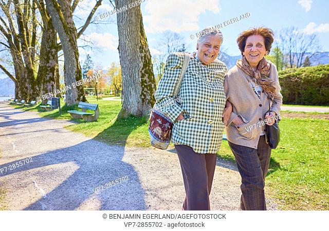 Lively senior woman walking in park, laughing heartily