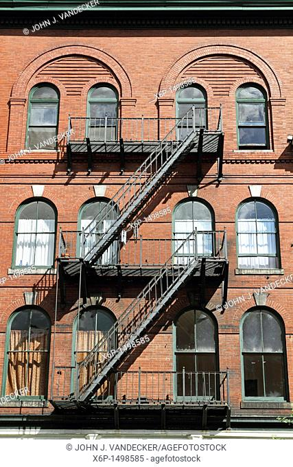An old building complete with fire escapes in downtown Bangor, Maine, USA  Bangor is the 3rd largest city in the state and the retail