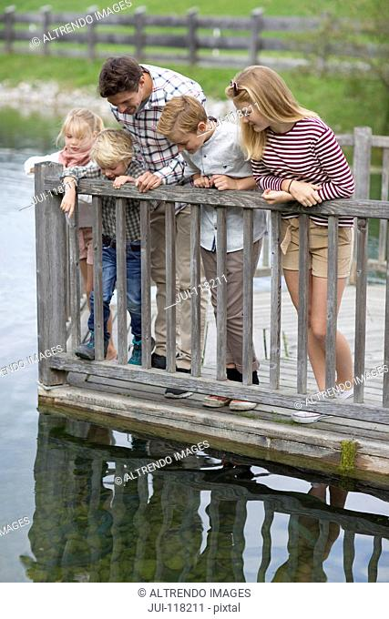 Father And Children Looking Into Water From Wooden Jetty