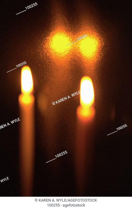 Two candles and their reflections surrounded by darkness