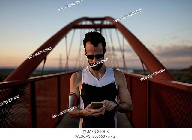 Runner using smartphone on a bridge at twilight