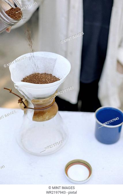 High angle view of a glass coffee maker, a conical jar with filter paper and coffee grounds