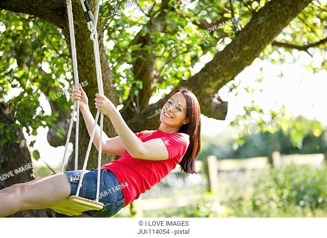 Portrait happy woman swinging on tree swing in sunny summer rural yard