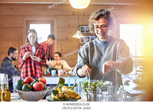 Woman tossing salad for friends in cabin
