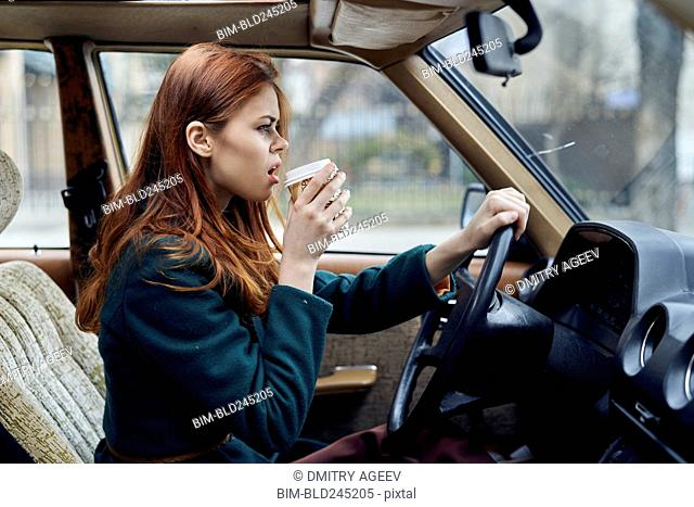 Angry Caucasian woman driving car and drinking coffee