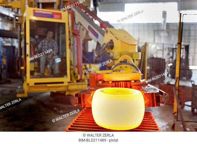 Caucasian worker operating steel melting machinery in factory